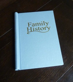 Metallic blue springback binder with Family History in gold lettering on the front and spine.